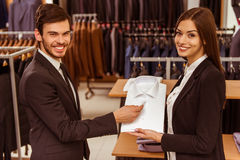 People in suit shop. Young beautiful female shop assistant consulting a modern young handsome businessman in the suit shop Stock Photo