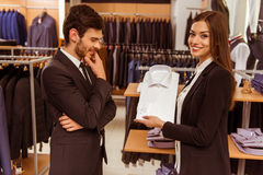 People in suit shop. Young beautiful female shop assistant consulting a modern young handsome businessman in the suit shop Royalty Free Stock Photo