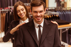People in suit shop. Young beautiful female shop assistant smiling and helping a modern young handsome businessman to try on a jacket in the suit shop Royalty Free Stock Photos