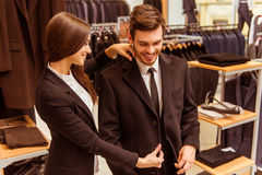 People in suit shop. Young beautiful female shop assistant smiling and helping a modern young handsome businessman to try on a jacket in the suit shop Royalty Free Stock Photo