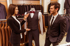 People in suit shop. Young beautiful female shop assistant smiling and offering a suit on a mannequin to a modern young handsome businessman in the suit shop Stock Images
