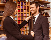 People in suit shop. Young beautiful female shop assistant smiling and offering a tie to a modern young handsome businessman in the suit shop Stock Images