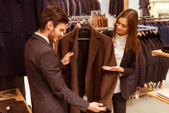People in suit shop. Young beautiful female shop assistant smiling and offering a suit to a modern young handsome businessman in the suit shop Stock Image