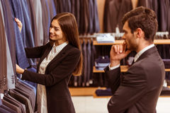 People in suit shop. Young beautiful female shop assistant smiling and offering a suit to a modern young handsome businessman in the suit shop Royalty Free Stock Photo