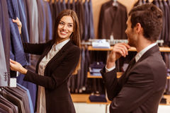 People in suit shop. Young beautiful female shop assistant smiling and offering a suit to a modern young handsome businessman in the suit shop Stock Photography