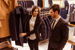 People in suit shop. Young beautiful female shop assistant smiling and offering a suit to a modern young handsome businessman in the suit shop Royalty Free Stock Images