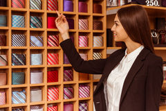 People in suit shop. Young beautiful female shop assistant smiling and pointing on different colourful ties while standing in the suit shop Stock Photography