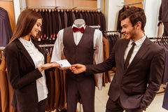 People in suit shop. Young beautiful female shop assistant smiling and showing cufflinks on a mannequin to a modern young handsome businessman in the suit shop Royalty Free Stock Photography