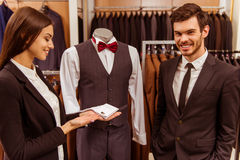 People in suit shop. Young beautiful female shop assistant smiling and showing cufflinks on a mannequin to a modern young handsome businessman in the suit shop Royalty Free Stock Images