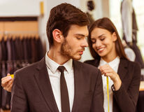 People in suit shop. Young beautiful female shop assistant taking measurements of a modern young handsome businessman in the suit shop Stock Photography