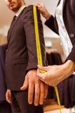 People in suit shop. Young beautiful female shop assistant taking measurements of a modern young handsome businessman in the suit shop Royalty Free Stock Photography