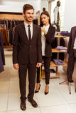 People in suit shop. Young beautiful female shop assistant taking measurements of a modern young handsome businessman in the suit shop Stock Image