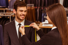 People in suit shop. Young beautiful female shop assistant taking measurements of a modern young handsome businessman in the suit shop Stock Images