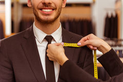 People in suit shop. Young beautiful female shop assistant taking measurements of a modern young handsome businessman in the suit shop, close-up Royalty Free Stock Photo