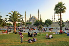 People at Sultanahmet. ISTANBUL - JUL 15: Muslims and Tourists enjoy the sun on Sultanahmet Square on Ramadan, July 15, 2013 in Istanbul, Turkey. At the end of Stock Photo