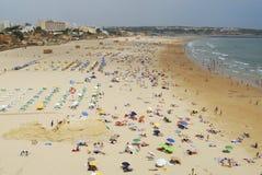 People sunbathe at Praia da Rocha beach in Portimao, Portugal. Stock Photo