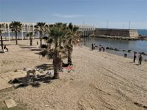Italy, the  Civitavecchia sea front. People sunbathe on the sand in front of the sea royalty free stock photography