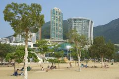People sunbathe at the Stanley town beach in Hong Kong, China. Royalty Free Stock Image