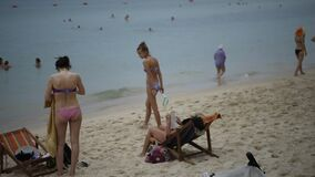 People sunbathe and swim.Some vacationers stroll along the shore. Pattaya,Thailand- February 20,2018: Sai Kaew Beach -Military Beach.People sunbathe and swim stock video footage