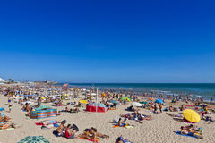 People sunbathing on Atlantic beach in Carcavelos, Portugal Stock Images