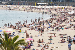 People sunbathing at beach in Barcelona Stock Images