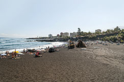 People sunbathing on beach garden. In Puerto de la Cruz in Tenerife. In the background are some houses of the village Royalty Free Stock Photography