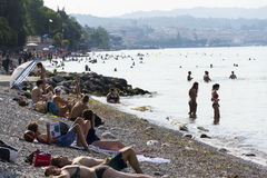 People sunbathing on beach on 30 July 2016 in Desenzano del Garda, Italy. royalty free stock images