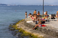 People sunbathing on beach on 30 July 2016 in Desenzano del Garda, Italy. royalty free stock photos