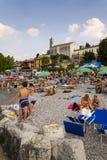 People sunbathing on beach on 30 July 2016 in Desenzano del Garda, Italy. DESENZANO DEL GARDA, ITALY - JULY 30: People sunbathing on beach on 30 July 2016 in stock photo