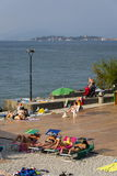 People sunbathing on beach on 30 July 2016 in Desenzano del Garda, Italy. DESENZANO DEL GARDA, ITALY - JULY 30: People sunbathing on beach on 30 July 2016 in royalty free stock photography