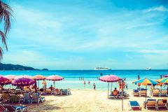 People are sunbathing on the beach. Many colorful sunshades and sun loungers on the beach in a sunny summer day. Summer royalty free stock images