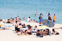 People sunbathing at Bogatell beach in Barcelona Royalty Free Stock Images