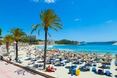 People sunbathing at Paguera Beach, Majorca, Spain. MAJORCA, SPAIN - MAY 31: People sunbathing at Paguera Beach, a spanish tourist village belonging to the royalty free stock photos
