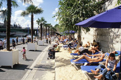 People sunbathing by the river Seine in Paris Royalty Free Stock Images
