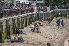 People sunbathing on the sandy beach at the side of the River Thames at South Bank. South Bank, Southwark, London, UK - August 6, 2014: Sandy beach at the side royalty free stock photos