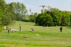 People sunbathing in spring in Kurpark Oberlaa, Vienna, with tower cranes in the background royalty free stock photo