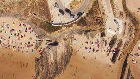People sunbathing under umbrellas on the beach aerial view. People and beach umbrellas on the beach aerial view stock video