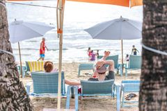 People on sunbed reading book under parasol at tropical Boracay. BORACAY ISLAND, PHILIPPINES - November 17, 2017 : People on sunbed reading book under parasol at Stock Photo
