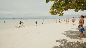 BORACAY, PHILIPPINES - JANUARY 5, 2018: People on a sunny white sandy beach of the Philippine tropics. Summer holidays. People on a sunny white sandy beach of stock video footage