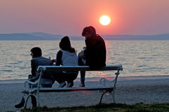 People in sunset on the horizon above sea Stock Photography