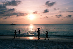 People at sunset on Palm Beach, Aruba. People walking at sunset on the Aruban beach, Palm Beach royalty free stock image