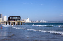 People Surfing and Swimming in Sea in Durban Stock Photo