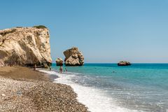 People swim at the beach next to a popular Aphrodite Rock in Cyprus Stock Photo