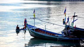 People swim in the kayak next to fishing boats. Royalty Free Stock Image