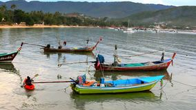 People swim in the kayak next to fishing boats. Royalty Free Stock Photography