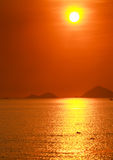 People swim in sea against sun in red sky above sea islands Royalty Free Stock Photo