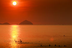 People swim in sea against sun in red sky above sea islands Royalty Free Stock Photography