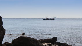 People Swim in Sea by Rock Beach Boat Drifts past stock video footage