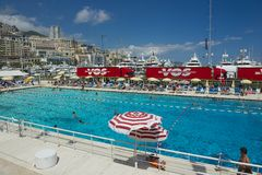 People swim and sunbathe at the open air public swimming pool in Monaco. Royalty Free Stock Photography