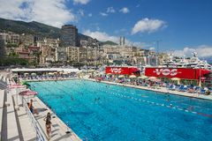 People swim and sunbathe at the open air public swimming pool in Monaco. Stock Photography